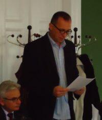 Mężczyzna czyta z kartki na posiedzeniu