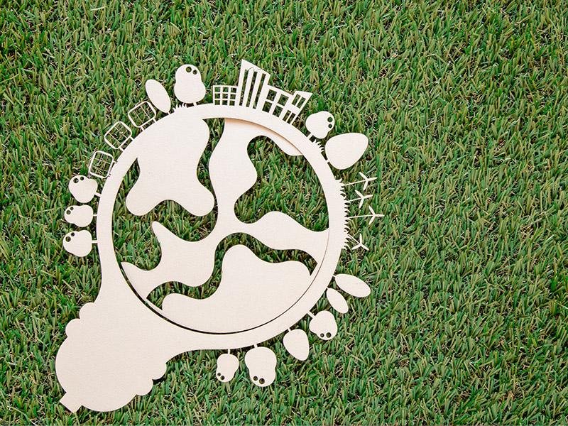 Planeta wycięta z papieru na zielonym trawniku