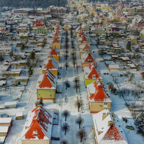 Qisok z góry na osiedle domów jednorodzinnych w zimowej scenerii
