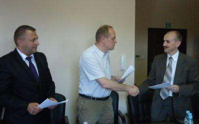 Trzech mężczyzn podpisuje umowę