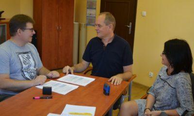 Trzy osobie rozmawiają przy stole