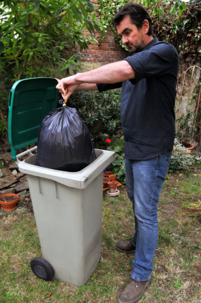 Mężczyzna wyrzuca śmieci do kontenera