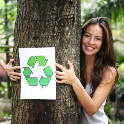 """Dziewczyna trzymająca drzewo ze znakiem """"recyklingu"""""""