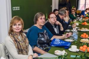 Grupa ludzi siedząca przy stole i słuchająca