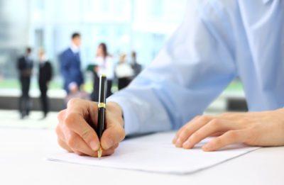 Osoba pisząca na kartce papieru