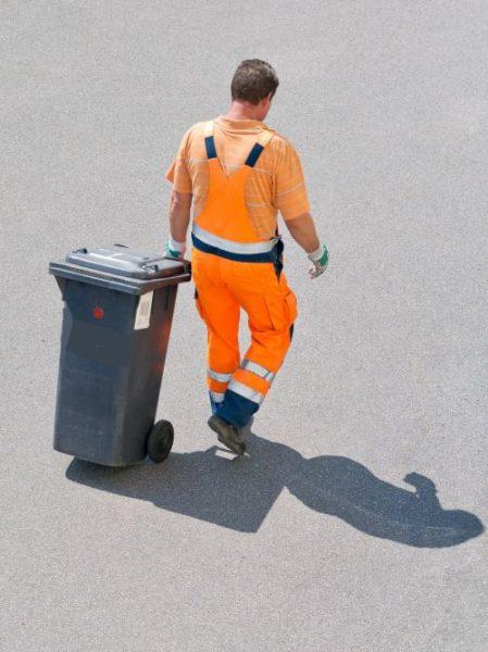 Mężczyzna wynoszący pojekmnik z odpadami